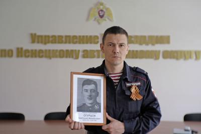Александр Огурцов с портретом деда-героя / Фото предоставлено автором